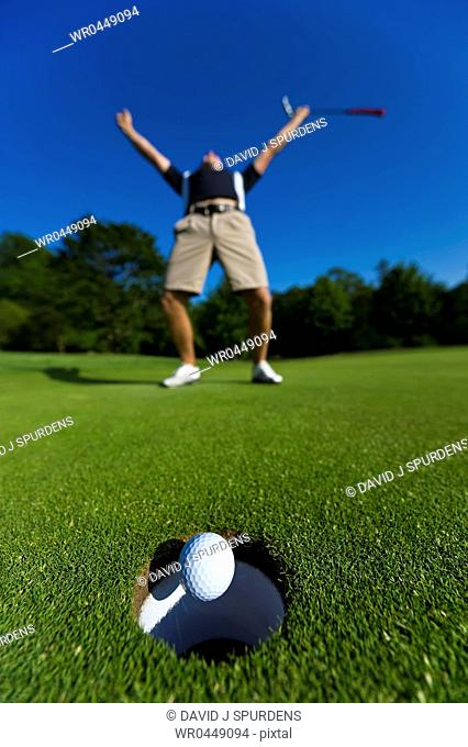 A Golfer celebrates a successful put