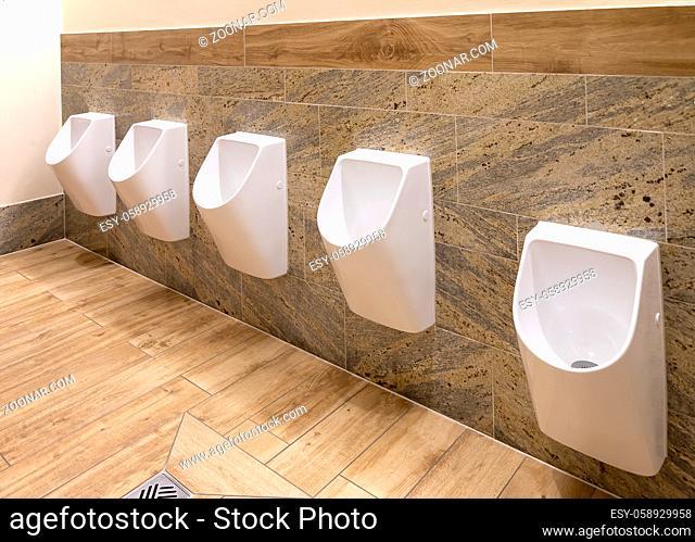 White urinals in men's bathroom, the design of white ceramic urinals for men in the toilet room. public men toilet room, WC