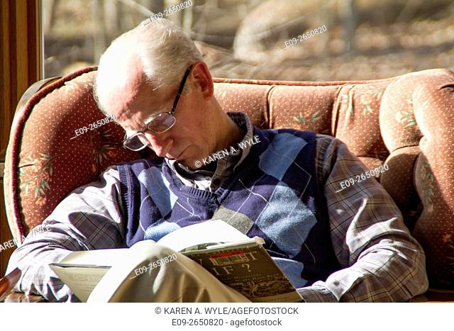 older man in glasses falling asleep in armchair in sunshine while reading, Monroe County, Indiana