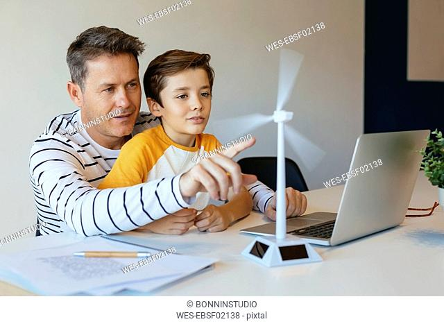 Father and son with laptop testing wind turbine model