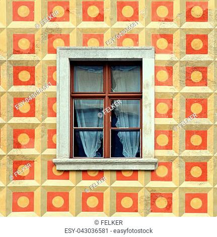 windows in the yellow and red pattern painted wall of old beautiful house, Budapest, Hungary. Square toned image