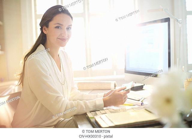 Portrait smiling interior designer with swatches at computer in home office