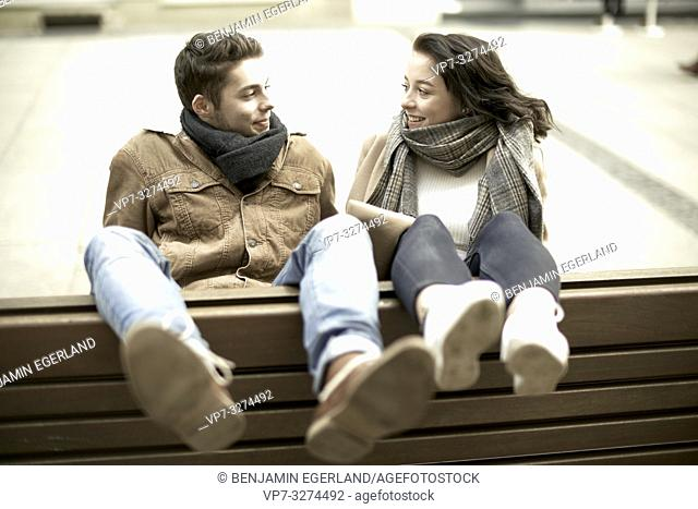 unconventional teenage man and woman sitting on bench the wrong way round in city, hanging out together, legs up, upside down, in Cottbus, Brandenburg, Germany