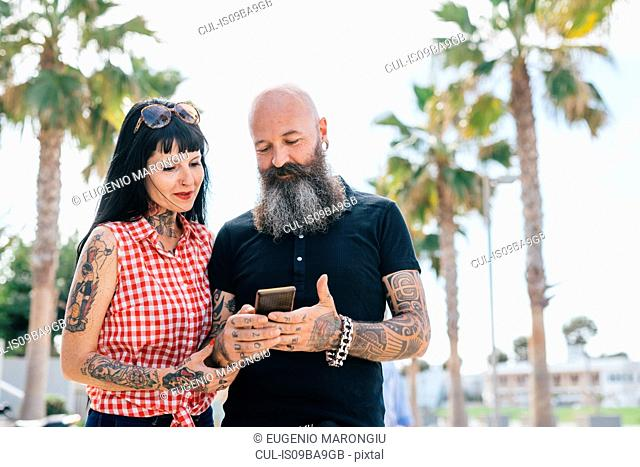 Mature hipster couple in park looking at smartphone, Valencia, Spain