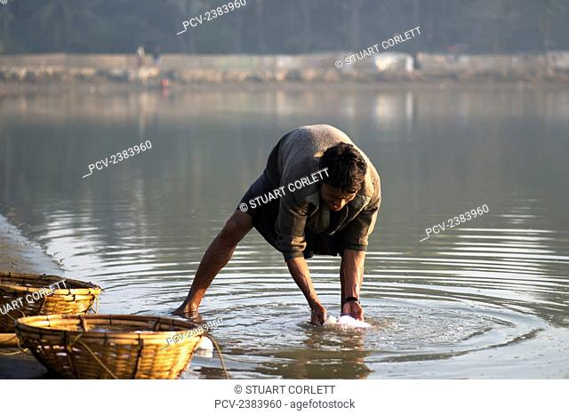 A fisherman washes a freshly caught fish in the water beside his baskets; Sittwe, Rakhine State, Burma