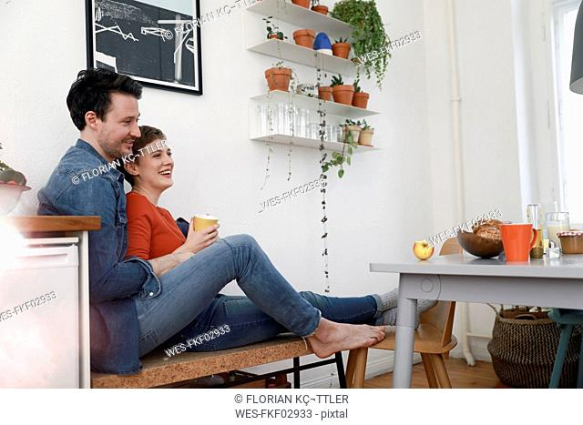 Happy couple sitting in kitchen, leaning against each other