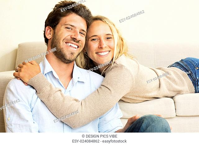 Happy young couple at home relaxing on the sofa