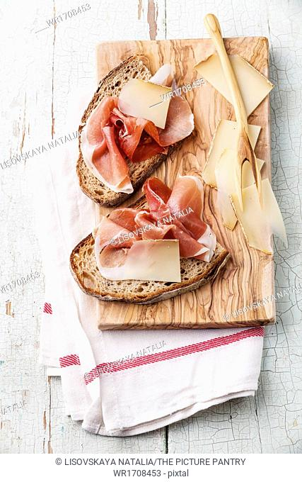 Bruschettas with cheese and ham on bread on blue wooden background