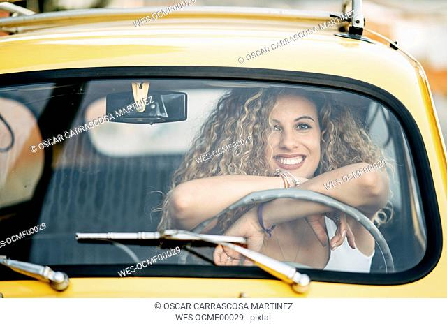 Portrait of happy blond woman in a classic car