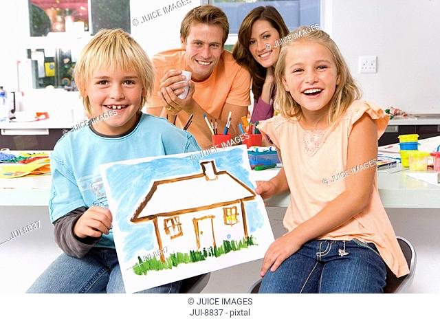 Boy and girl 6-8 holding up painting of house, parents in background, smiling, portrait