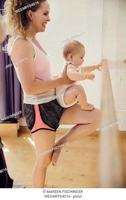 Two mothers holding up their small children to barre in dance studio
