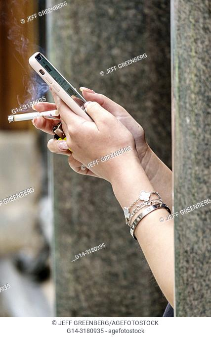 United Kingdom Great Britain England, London, Mayfair, cigarette, smoking smoke, outdoor sidewalk, woman's hands, using smartphone, nicotine addiction, texting