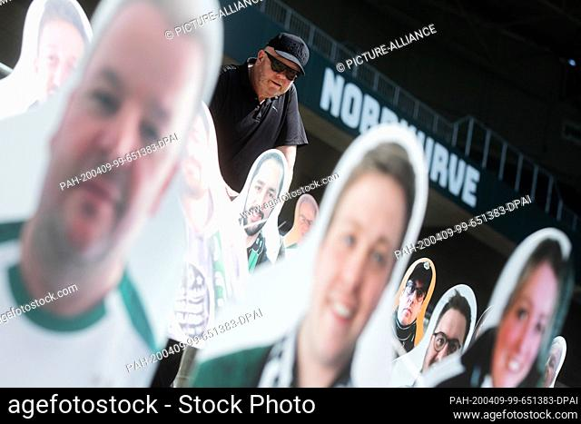 "09 April 2020, North Rhine-Westphalia, Mönchengladbach: Fan representative Thomas """"Tower"""" Weinmann stands between the first """"cardboard comrades"""" - fans of..."