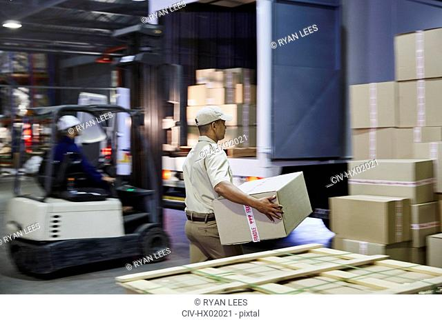 Workers and forklift loading cardboard boxes onto trucks at distribution warehouse loading dock
