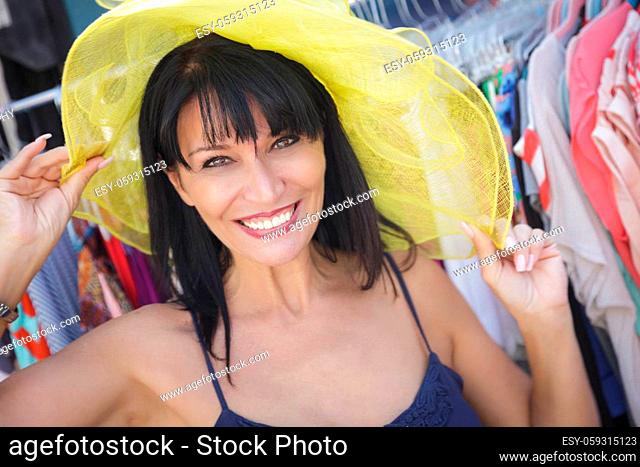 Pretty Italian Woman Trying on Yellow Hat at the Street Market