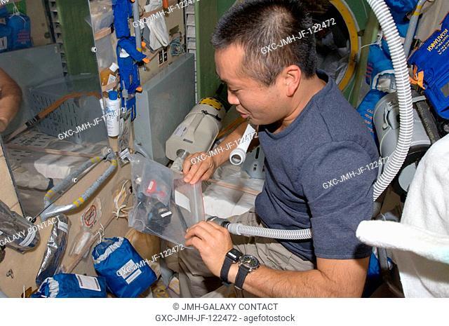 Japan Aerospace Exploration Agency (JAXA) astronaut Koichi Wakata, Expedition 1819 flight engineer, returns scissors and hair clippers to their storage bag...