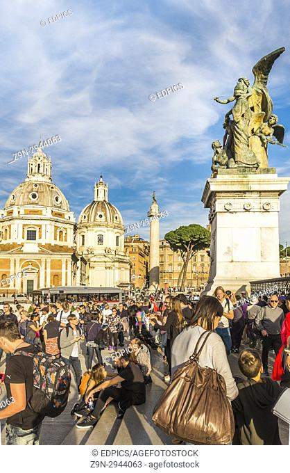 tourists at piazza venezia in front of bronze sculpture at the entrance to monumento nazionale a vittorio emanuele II, santa maria di loreto and santissimo nome...