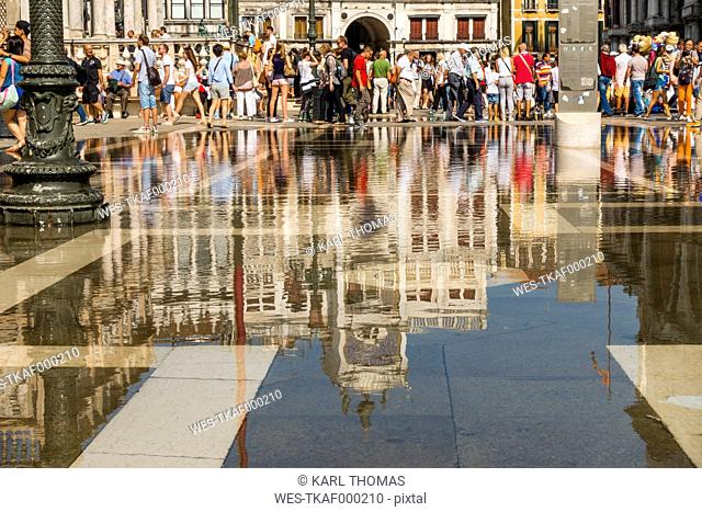 Italy, Veneto, Venice, Piazza San Marco, Torre dell'Orologio and tourists, water reflection