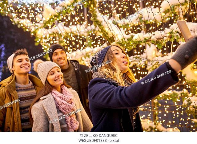 Happy friends in winter decoration taking a selfie