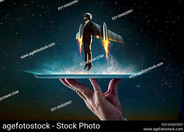 Waiter hand holding an empty digital tablet with Businessman wear a rocket suit to lift , Business success concept