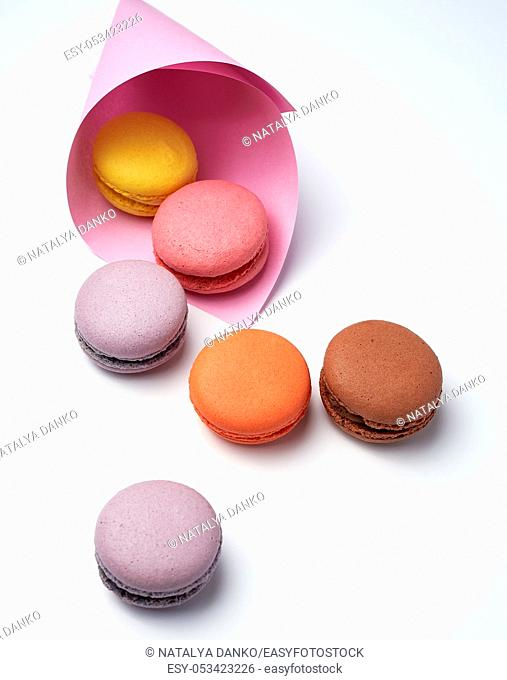 baked macarons in a pink paper bag on a white background, close up