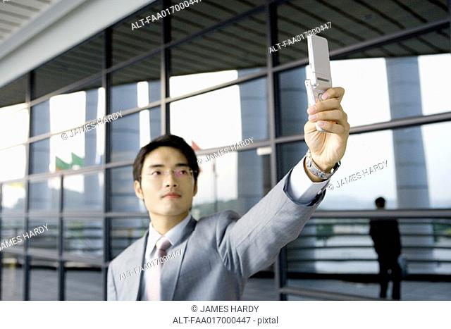 Businessman taking photo with cell phone