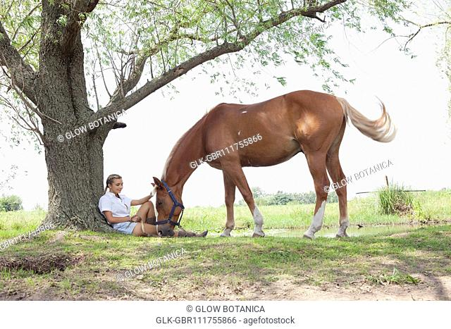 Woman relaxing in a field with a horse standing near her