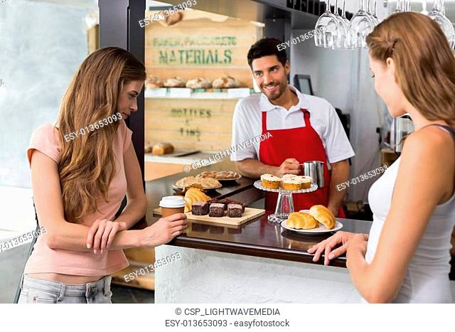 Women looking at sweet food at coffee shop