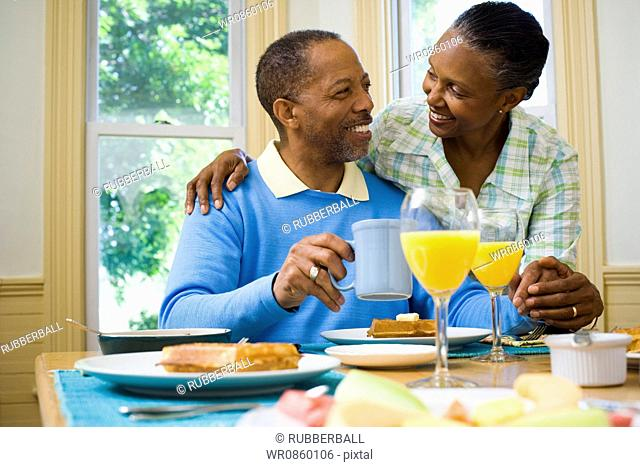 Senior man and a senior woman smiling at the breakfast table