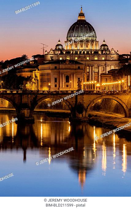 St. Peter's Basilica and Tiber River illuminated at dusk, Rome, Lazio, Italy