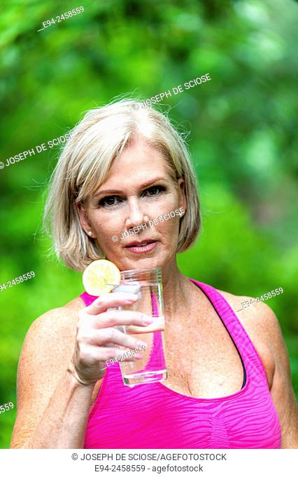 56 year old blond woman holding a glass of water to her head to cool off