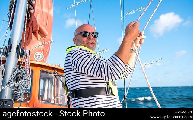 Eins Skipper auf seiner Yacht setzt die Segel. A skipper is rigging his sailing boat