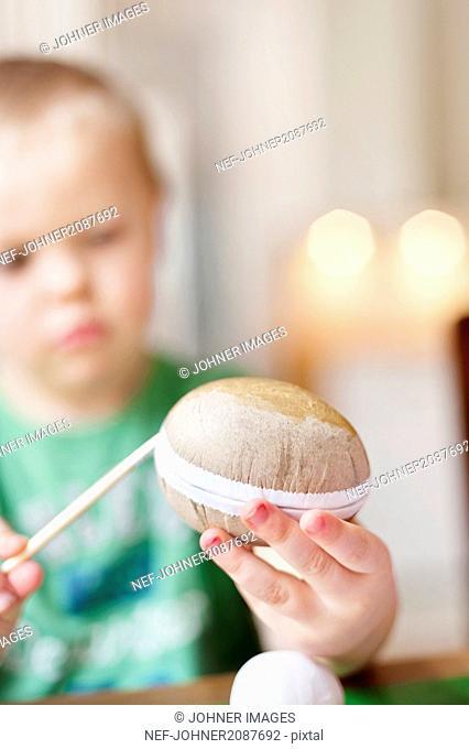 Boy decorating Easter egg