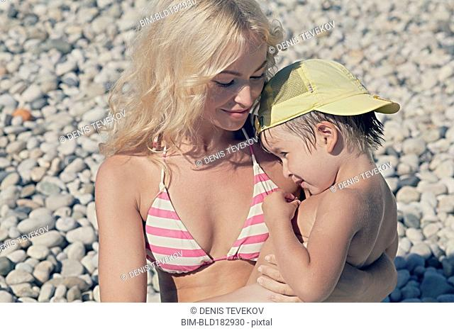 Mother holding son on rocky beach