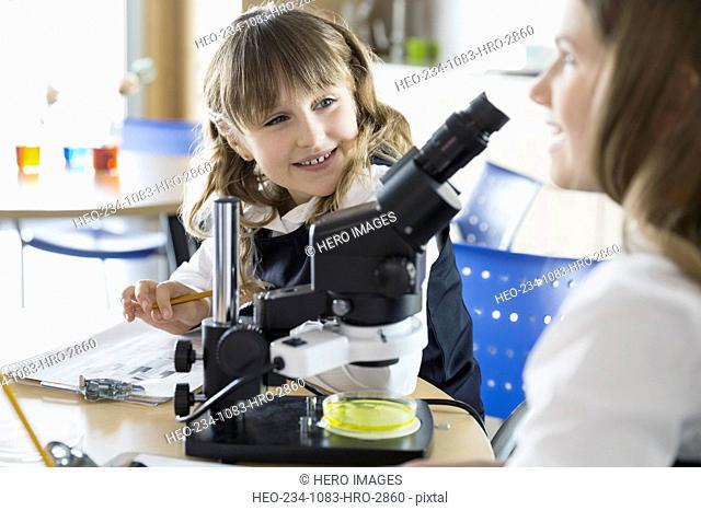 School girls using microscope in science classroom