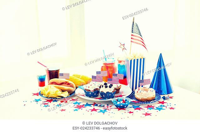 national holidays, celebration, food and patriotism concept - close up of hot dog with american flag decoration, potato chips and drinks on 4th july at home...