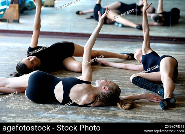 Three young ballet dancers on the floor rehearsing position in the ballet