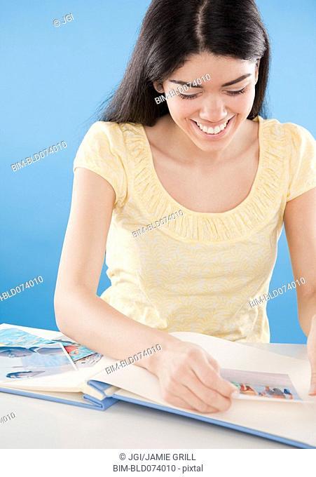 Hispanic woman putting photographs in album