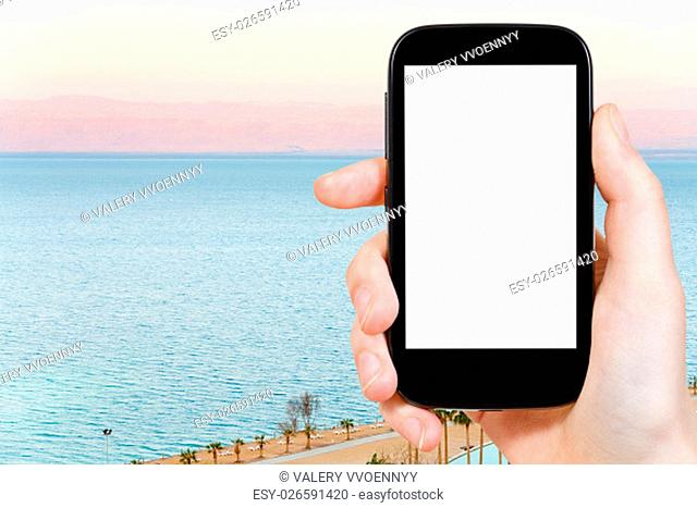 travel concept - tourist photographs sunrise over calm Dead Sea on smartphone with cut out screen with blank place for advertising
