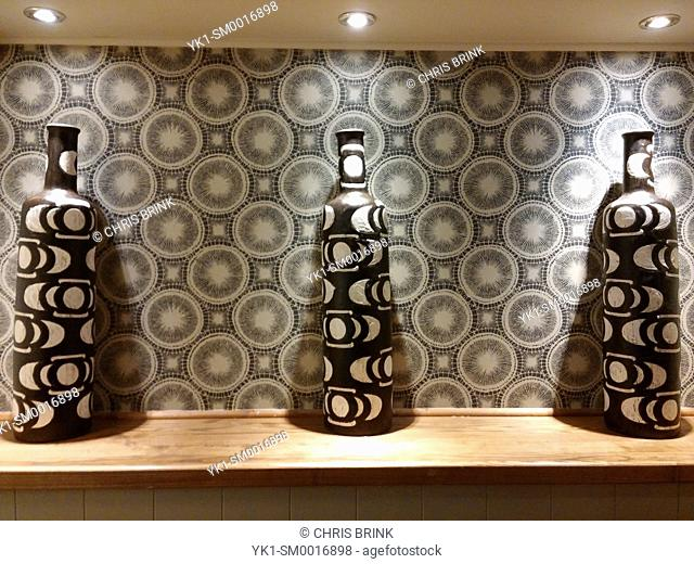 Wallpaper with matching vases in a pub England UK