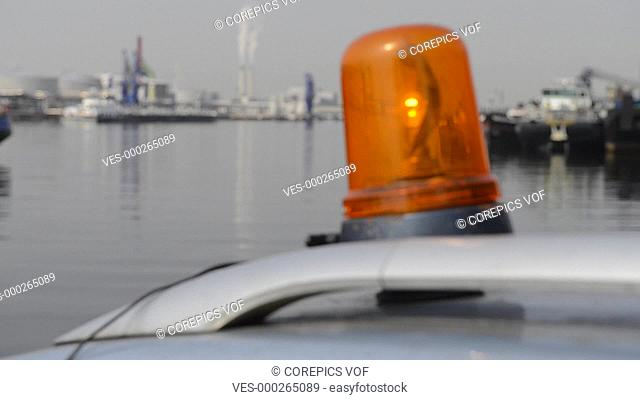 An orange flashlight on top of a car in an industrial harbor, zooming out
