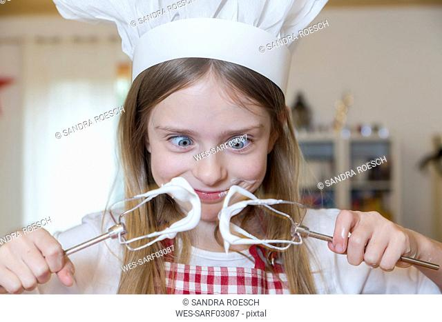 Portrait of staring girl with stirrer and chef's hat