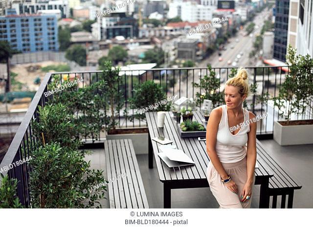 Caucasian woman standing on balcony