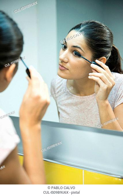 Woman applying mascara in front of mirror