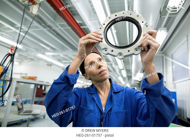 Female helicopter mechanic examining disc in airplane hangar