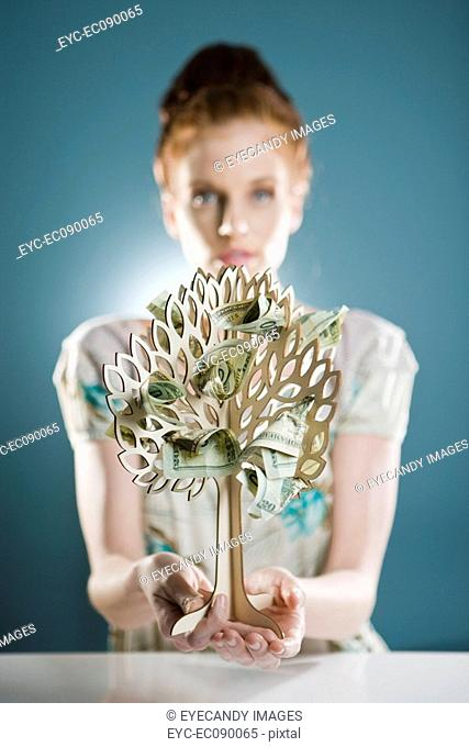 Portrait of young woman sitting by toy money tree on table