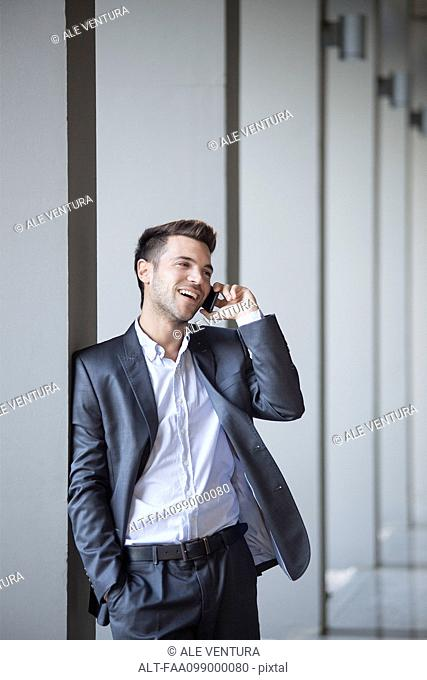 Young man leaning against buiding column talking on cell phone