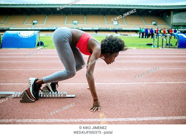Young black athlete preparing for race in stadium