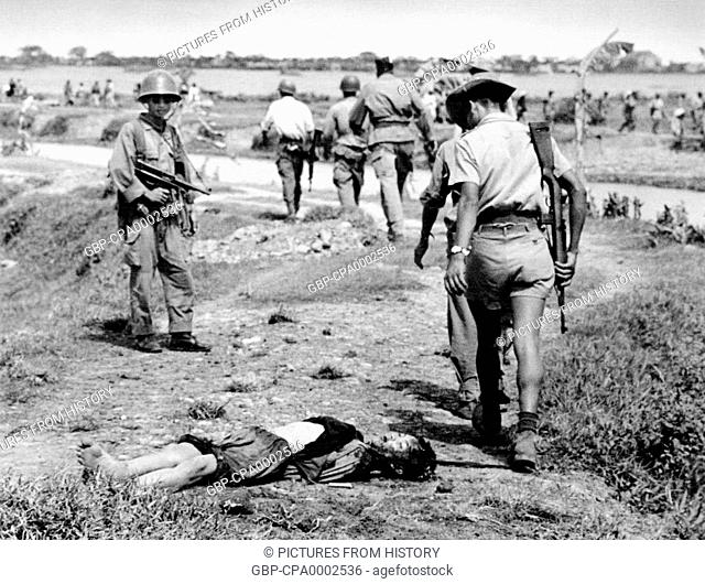 Vietnam: French colonial forces pass the body of a dead child on the road between Nam Dinh and Thai Binh, north Vietnam, 1954