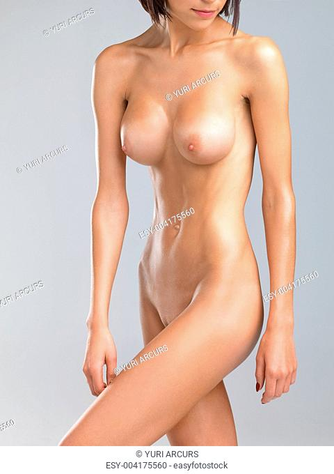 Beautiful young nude woman standing isolated on a grey background